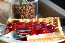Waffles with cherries and coffee beans in the background