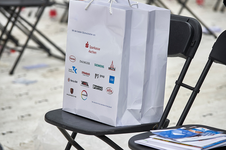 Paper bag adorned with sponsor logos